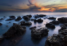 De zwarte rots op het strand stock afbeeldingen