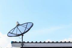 De zwarte satelliet installeert op het huisdak met blauwe hemel stock foto