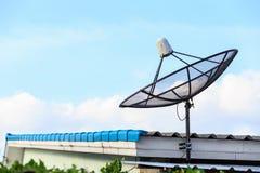 De zwarte satelliet installeert op het huisdak met blauwe hemel stock foto's