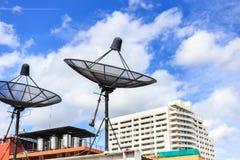 De zwarte satelliet installeert op het huisdak met blauwe hemel stock afbeelding