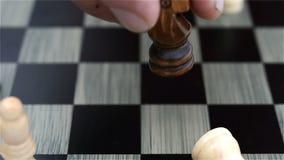 De zwarte schaakspeler haalt de witte koning neer stock videobeelden