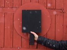 De zwarte scherpe raad hield ter beschikking op rode geweven houten backgrou Royalty-vrije Stock Afbeeldingen