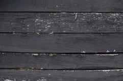 De zwarte schil doorstond horizontale houten raad met stro stock afbeeldingen