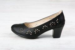 De zwarte schoen van leervrouwen ` s op witte houten achtergrond Stock Foto