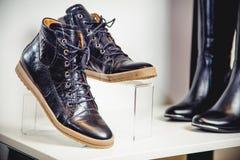 De zwarte schoenen van het octrooileer liggen op de plank Stock Afbeelding
