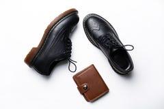 De zwarte schoenen van de leerderby met polyurethaanzolen en een bruine beurs met een knoop op een witte achtergrond stock fotografie