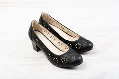 De zwarte schoenen van leervrouwen ` s op witte houten achtergrond Stock Afbeelding