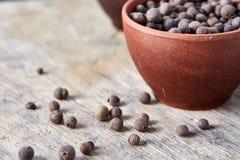 De zwarte sesamzaden in een klei werpen met verspreide zaden op houten vat, close-up, ondiepe diepte van gebied royalty-vrije stock fotografie