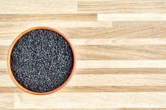 De zwarte sesamzaden in een klei werpen op gestripte houten geweven achtergrond, close-up, hoogste mening stock afbeelding
