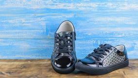De zwarte sportieve stijl van babyschoenen op de houten vloer, de blauwe houten muur Royalty-vrije Stock Foto