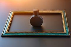 De zwarte steenfles voor unisex-parfumclose-up binnen smaragdgroen kader met gouden grens op een donkere achtergrond, bespot omho royalty-vrije stock fotografie