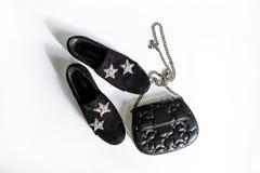 De zwarte su?deschoenen met een bergkristal spelen decoratie en een zwarte koppeling op een ketting met sterren op een witte acht stock fotografie