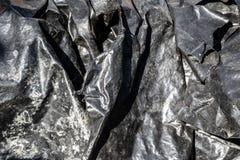 De zwarte textuur van de folie plastic oppervlakte royalty-vrije stock afbeeldingen