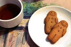 De zwarte thee en peperkoekmensenkoekjes in een wit werpen in een koffie Royalty-vrije Stock Foto