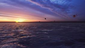 De zwarte vlieg van haviks militaire helikopters bij zonsopgang over het grenzeloze overzees stock video