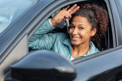 De zwarte vrouw die van de autobestuurder tonend nieuwe autosleutels en auto glimlachen stock fotografie