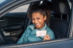 De zwarte vrouw die van de autobestuurder tonend nieuwe bestuurders` s vergunning glimlachen stock fotografie