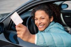 De zwarte vrouw die van de autobestuurder tonend rijbewijs glimlachen royalty-vrije stock foto