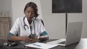 De zwarte vrouwelijke arts zit bij een bureau kijkend aan camera, het Afrikaanse Amerikaanse verpleegsterswerk op laptop in moder stock afbeelding