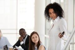De zwarte vrouwelijke mentor maakt presentatie op flipchart opleidend empl stock afbeelding