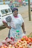 De zwarte Zoeloes vrouw met stammenmake-up op haar gezicht verkoopt groenten in Zoeloes dorp in Zoeloeland, Zuid-Afrika Royalty-vrije Stock Foto