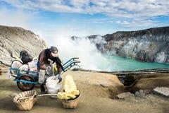 de zwavel-geladen manden zijn hand-carried van de kratervloer De vulkaan van Kawahijen in Java, Indonesië royalty-vrije stock afbeeldingen
