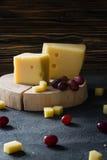 De Zweedse harde gele kaas met gaten hakte met rode druiven op houten plakken Stock Foto