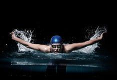 De zwemmer van de Profesionalvrouw zwemt gebruikend schoolslagtechniek op de donkere achtergrond Stock Afbeeldingen