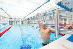 De zwemmer van de sport het winnen De mens die toejuichend het vieren overwinningssucces glimlachen gelukkig in pool het dragen z Stock Foto