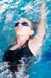 De zwemmer zwemt binnen ontmoet het doen van rugslag Stock Foto