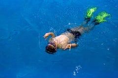 De zwemmer zwemt op zijn rug met zijn handen die het teken van overwinning tonen stock foto