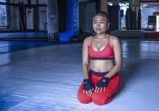 De zwetende Aziatische vrouw in sport kleedt zich ademhaling en het uitrekken na harde opleidingsfitness training het ontspannen  stock foto's