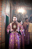 Deacon stands with a holy book. Deacon in gold and violet robe  stands with a holy book. Orthodox liturgy with bishop Mercury in High Monastery of St Peter in Royalty Free Stock Photos
