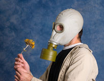 Dead. Concept image of death featuring a young man wearing a gas mask and holding a wilted flower Stock Photography