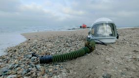 Dead astronaut on the planet. The skull from the head in the helmet lies on the sand by the sea. Troubled by accident.