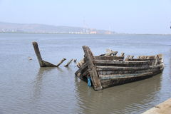 Dead Boat in Water Grave yard. Old fishing boat broken lying in high tide water due to water level increase Stock Image