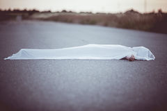 Dead body covered with sheet in middle of road Royalty Free Stock Photo