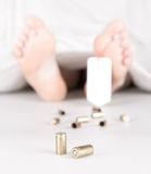 Dead body with toe tag. Bullets and a white sheet Stock Images