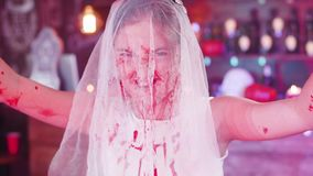 Dead bride costume bloody-stained before a halloween party. Brides veil on her face painted in blood. Scary dress as a disguise stock video footage