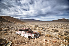 Dead Car in Death Valley. An old, rusted car sits under cloudy skies in Death Valley National Park, California Royalty Free Stock Photos