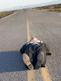Dead centered. Business man lays down in the middle of the road, in a black suit, in the middle of the desert Stock Photo