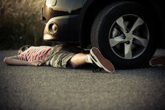 Dead child laying on street in front of car Stock Photos