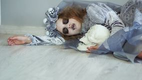 A dead dracula bride lies on the floor hugging a skull with one eye. Suddenly, she comes to life, opens her eyes. Child. In halloween costume stock video