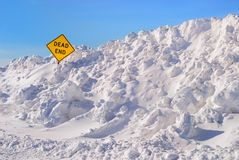 Dead End. Large plowed snowbank surrounding a dead end sign royalty free stock photography