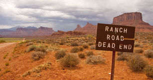 Dead end ranch road. A long dead end dirt ranch road in the desert with mountains and buttes in the background stock image