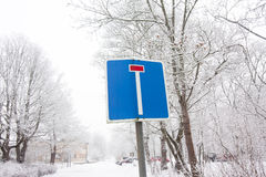 The Dead End road sign on winter sky and trees background. royalty free stock image