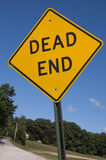 Dead End Sign. A dead end sign stands against a blue sky, with a diagonal horizon in the background Royalty Free Stock Images