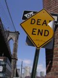 Dead End Sign and Brooklyn Bridge. Dead end and one way signs against a brick wall and Brooklyn Bridge, as seen from Brooklyn side facing Manhattan, NYC royalty free stock images