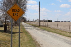 Dead end sign on a straight country road. Dead end sign on a long straight country road on a beautiful sunny day Stock Images