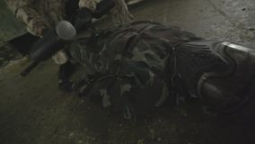 Dead Enemy on the Floor. Paintball player in protective uniform jamping down near dead body of the enemy lying on the floor in a mask and camouflage with a gun stock video footage